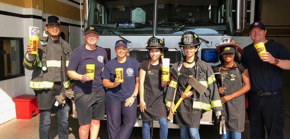 Firefighters Pose with Big Yellow Cup