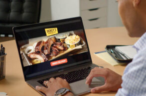 man ordering food on laptop from dickey's barbecue pit franchise